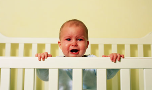 baby standing in crib crying