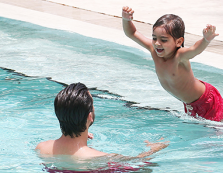 Child jumping to Dad in pool
